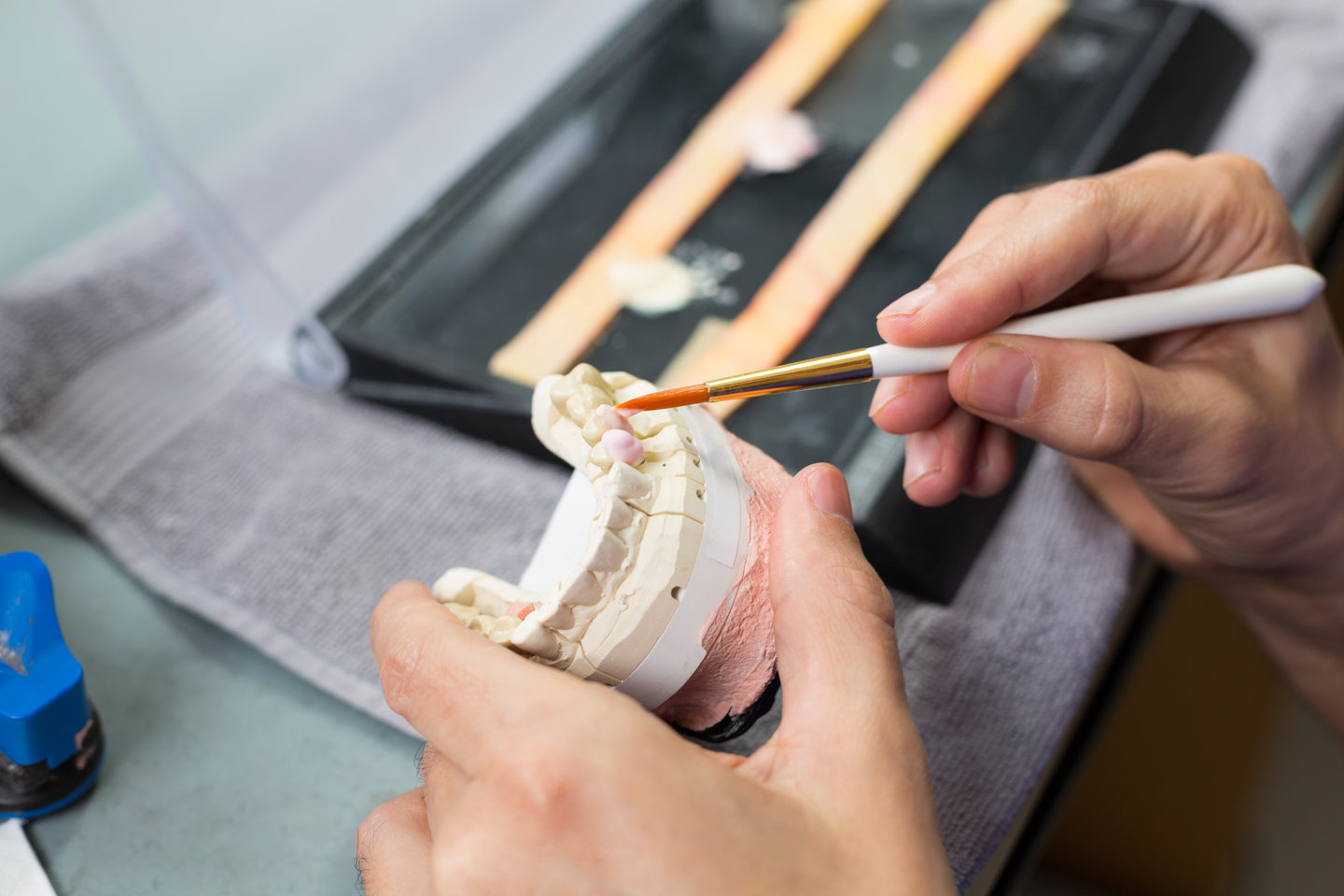 Closeup of a dental technician applying porcelain to a dentition mold with a brush in a lab